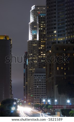 A dramatically underlit skyscraper in downtown LA.  Shot with a long exposure from a pedestrian bridge.
