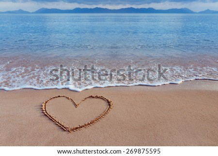 A drawing of a heart as a love symbol on a yellow sand at a seascape background. - stock photo