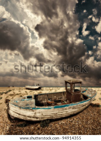 a dreamy, almost grunge style image of the wrecked fishing boats abandoned to rot away on the shingle beach at dungeness in south east england. A beautiful dramatic sky goes away to the horizon. - stock photo