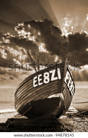 a dreamy, atmospheric, toned image of a wooden fishing boat on a shingle beach with a beautiful moody sky in the background. Registration number is false. - stock photo