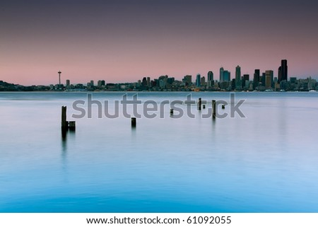 A dreamy look of a city skyline with skyscrapers shot from a beach with some old pier logs in the foreground. Long exposure creates a creamy water surface of waves and ripples. - stock photo