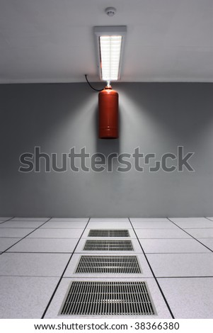A dreamy shot of a server/data center with air-conditioner grids and a fire suppression system including ozone friendly gas bottle and a smoke detector. - stock photo