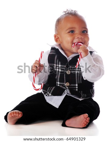 A dressed-up baby boy happily chewing on a candy cane while holding another.  Isolated on white.