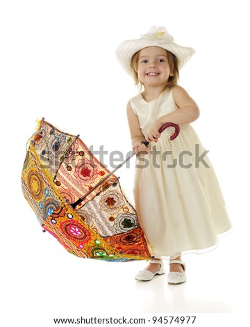 A dressed-up toddler attempting to raise a multicolored parasol.  On a white background. - stock photo