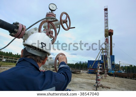 A drilling rig worker. Focus is on the instruments. - stock photo