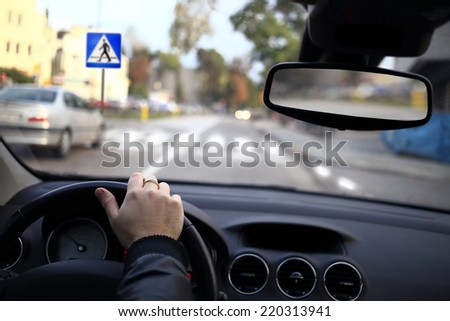 A driver approaching a pedestrian crossing - stock photo