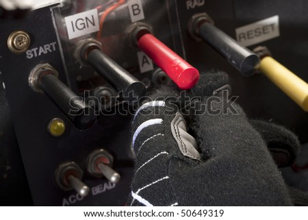A driver flips the switches to start up his stock car - stock photo