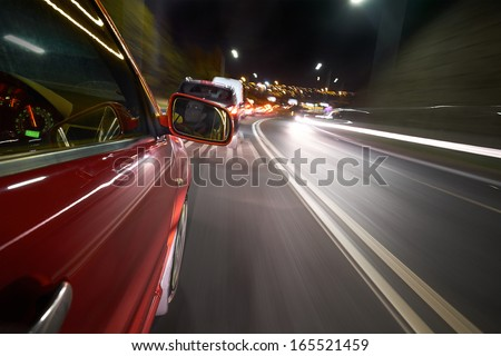 A driver stuck in a traffic jam on a busy road at night. - stock photo