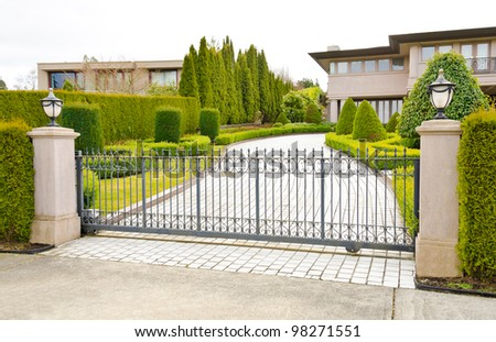 A driveway to the luxury house behind the gates in suburbs of Vancouver, Canada - stock photo