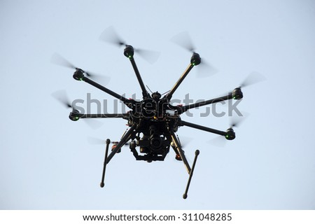 A drone with a camera flying high above a residential area