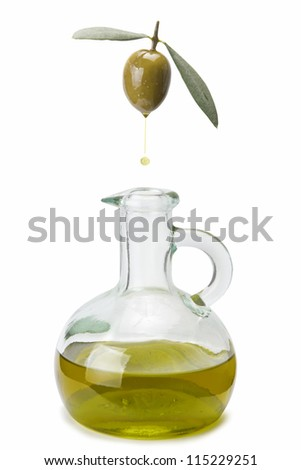 A drop of olive oil falling from one olive into a bottle - stock photo