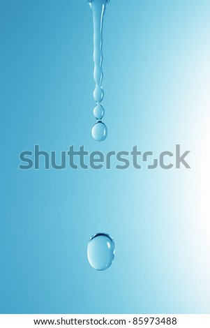 A drop of water on a blue gradient background - stock photo