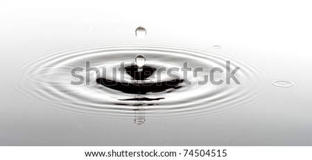 A drop ripples through the pure water - stock photo