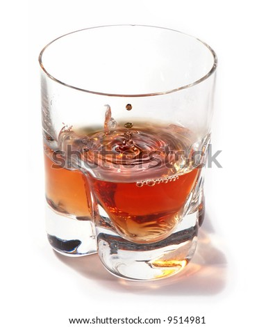 A drop splashing in a glass of whiskey - stock photo