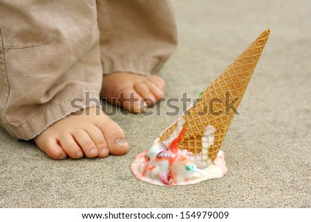 a dropped rainbow colored ice cream cone lays upside down on the sidewalk at the feet of a young child - stock photo