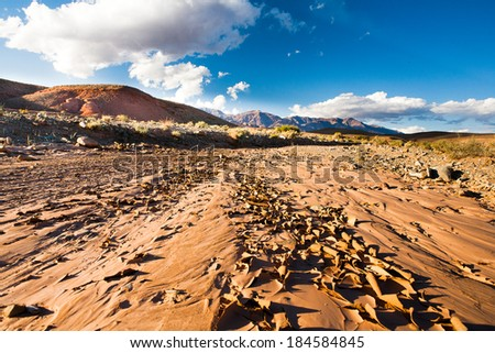 A drought stricken landscape of cracking earth surface - concept image of global warming. Background blue sky, green hills, clouds. - stock photo