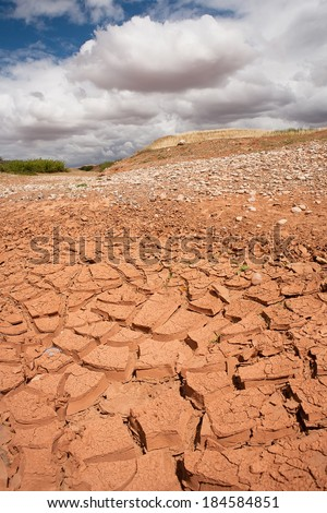 A drought stricken landscape of cracking earth surface - concept image of global warming. Background blue sky, green hills, clouds.