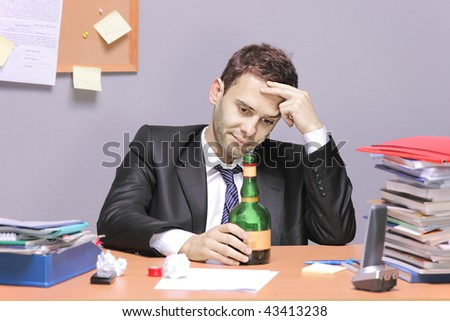 A drunk businessman in the office - stock photo