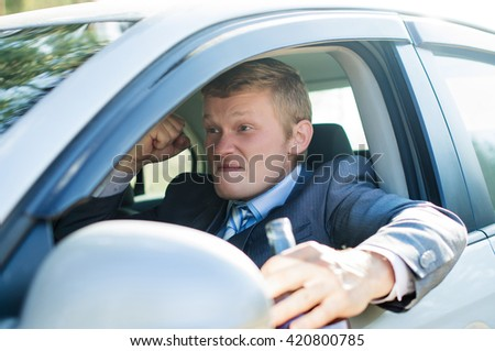 A drunk driver behind the wheel of of the car - stock photo