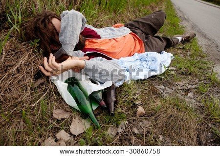 A drunk homeless man laying the ditch - stock photo