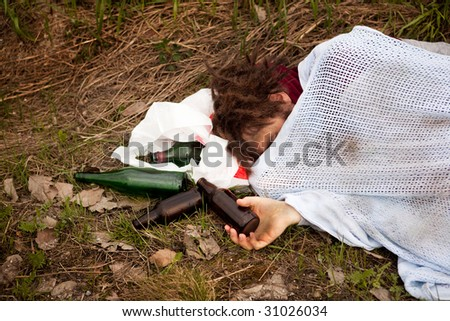 A drunk homeless man sleeping in a ditch - stock photo
