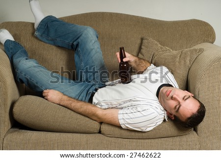A drunk man is passed out on the couch from drinking too much beer - stock photo