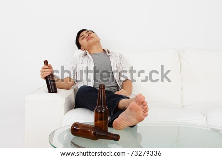 A drunk man on a sofa with beer bottles - stock photo