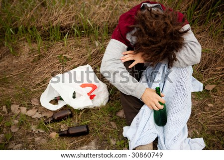 A drunk person sitting in a ditch with a wine bottle - stock photo