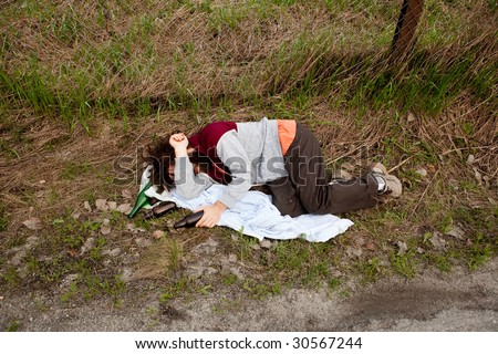 A drunk unemployed person laying in the ditch - stock photo