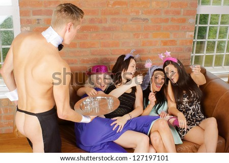A drunken bachelorette or hen night party with a cheeky butler waiter - stock photo