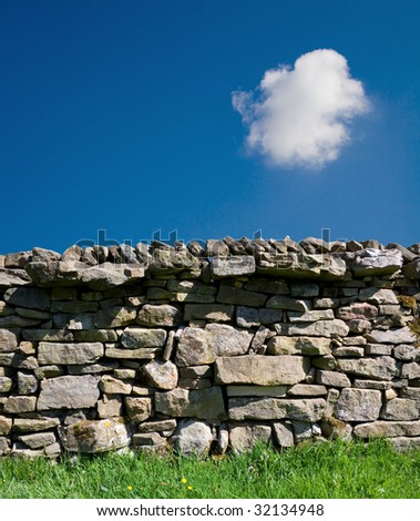 A dry stone wall against a blue sky with copy space.