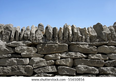 A dry stone wall against clear blue sky. Space for text. - stock photo