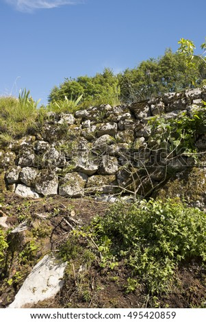 a dry stone wall in amongst agricultural scenery in the Trentino wolds Italy under a clear blue sky in autumn