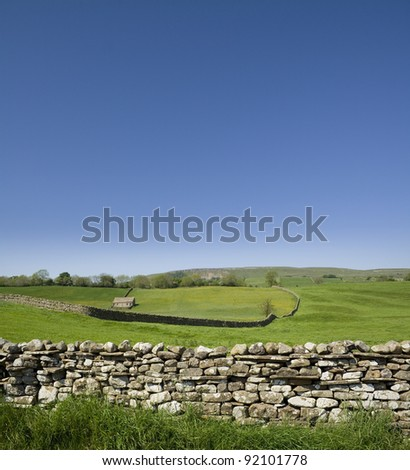 A dry stone wall snaking across The Yorkshire Dales. - stock photo