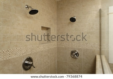 A dual controlled shower area with a half wall and a glass partition that looks into the rest of the bathroom. Horizontal shot. - stock photo