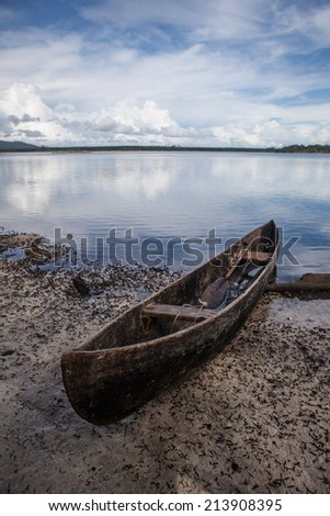 A dugout canoe, owned by a local fisherman, has been pulled up onto a remote beach in the Solomon Islands. Many islanders continue to use dugout canoes as their main form of transportation. - stock photo