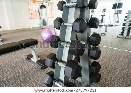 A dumbbell rack with dumbbells - stock photo
