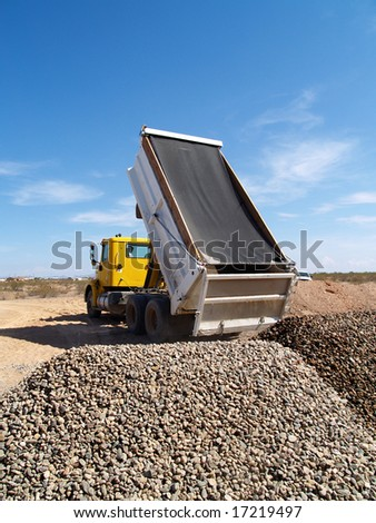 A dump truck is dumping gravel on an excavation site.   Vertically framed shot. - stock photo