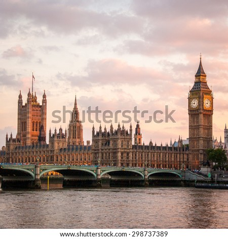 A dusk view over the River Thames, London, of the Palace of Westminster, the seat of UK government.  Big Ben is visible to the right and Westminster Bridge in the foreground. - stock photo