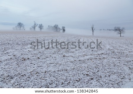 A dusting of snow on barren fields - stock photo