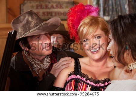 A dusty cowboy tries to talk to two lovely barmaids in the saloon. - stock photo