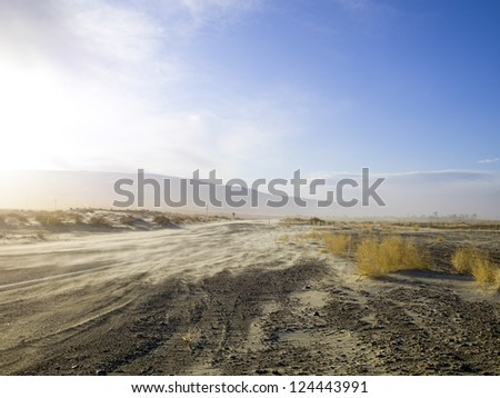 A dusty desert road with tumble weeds, under a beautiful blue sky.