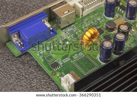 A dusty green computer component. Detail of a dusty computer mainboard. Electronic components on the printed circuit board. - stock photo