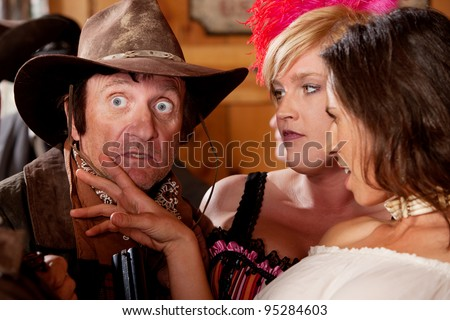 A dusty old cowboy is surprised by the two dangerously beautiful barmaids. - stock photo
