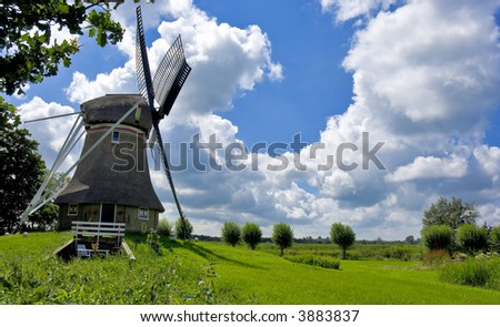 A dutch windmill inside a rural environment