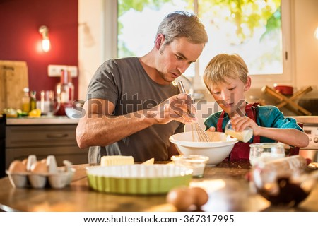 A eight years old blond boy with a red apron is cooking  with his father in a luminous kitchen. They are sitting at a wooden table the dad is mixing the preparation while his son is adding ingredients - stock photo