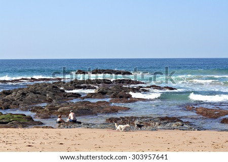 A elderly couple relax in a rock pool on a sunny day at the beach. - stock photo