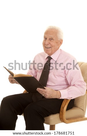 a elderly man in his pink shirt and his tie with a smile holding on to a book.