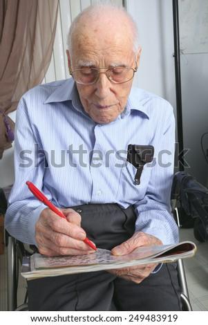 A elderly man sitting doing crosswords hobby - stock photo