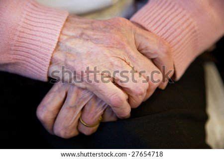 A elderly woman crosses her hands politely, wearing a pink sweater in her nursing home care center. - stock photo